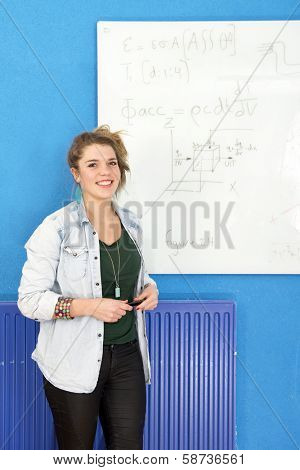 Smart student standing next to a complex differential equation, she's just solved on the white board behind her poster