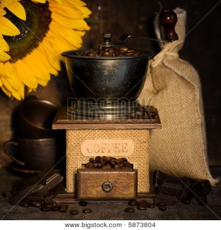 Stiill life with Antique coffee grinder burlap sack coffee cups chocolate and sunflower on rustic table poster