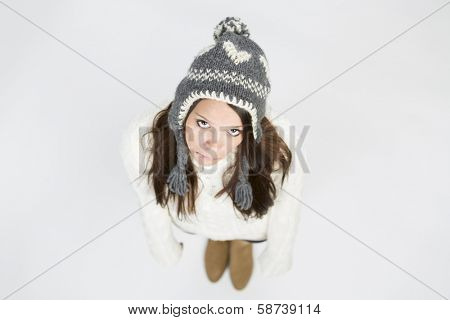 Upset young woman in warm winter clothing and grey cap, standing with arms hanging down and looking up with sadness, isolated on grey background.