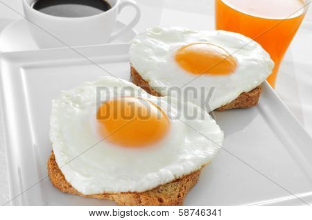 somme heart-shaped fried eggs served on bread, a cup of coffee and a glass of orange juice on a set table