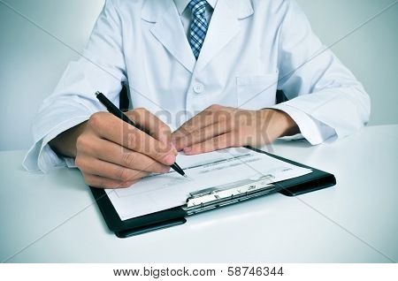 a doctor sitting in the desk of his consulting room writing in a clipboard