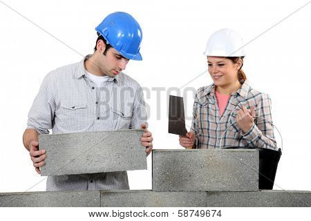 Bricklayer and apprentice with a block wall