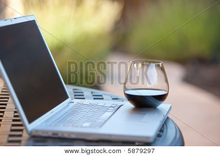 glass of red wine on a laptop computer in garden