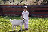 Little girl (3 years old) stroking a goat on farm. poster