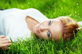 Portrait of beautiful young woman lying on a fresh green lawn poster