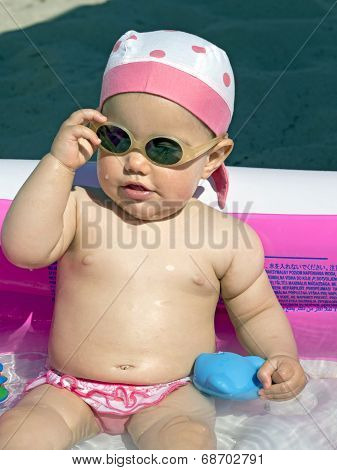 Baby Girl Takes Off   Sunglasses Inside An Inflatable Pool On The Beach