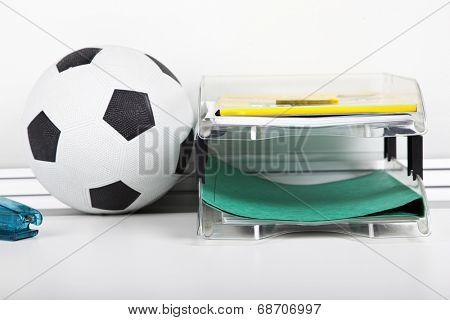 Soccer ball near file rack at desk