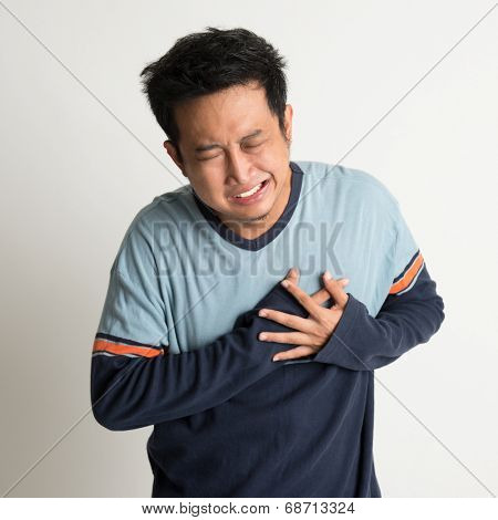 Asian male heartache, pressing on chest with painful expression, on plain background