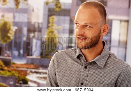 Closeup photo of young bristly man outdoors, smiling, looking away.