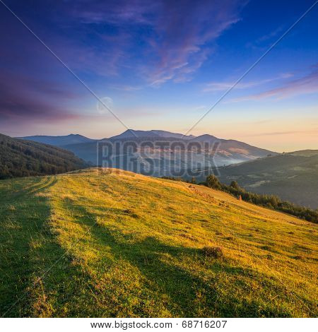 Pair Of Haystacks And Trees At Mountain At Sunset