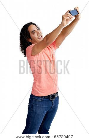 Mixed race man in casual clothing taking a selfie with his cameraphone in studio