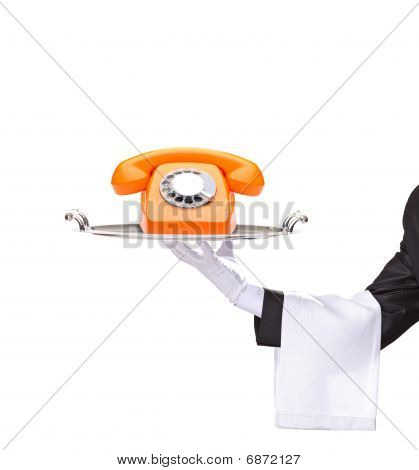 Hand holding a silver tray with an orange telephone on it