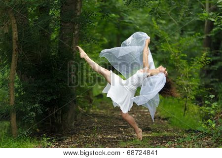 Mystical portrait of a beautiful graceful barefoot woman in a fresh white dress with her arms draped in filmy sheer fabric posing with one leg raised against a lush green woodland backdrop