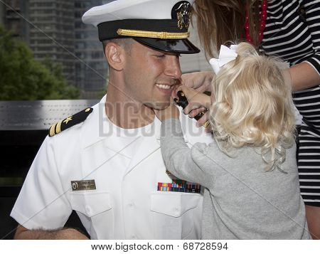 NEW YORK - MAY 23, 2014: US Navy Lt. Christopher Mikell's daughter fastens new shoulder boards to his uniform during his promotion ceremony at the National September 11 Memorial site.