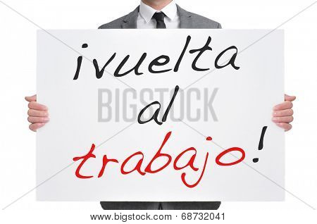 businessman holding a signboard with the text vuelta al trabajo, back to work in spanish, written in it poster