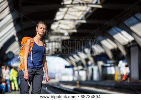 Pretty, young woman in a trainstation, waiting for her train, boarding a train (color toned image)