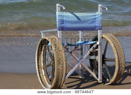 ingenious wheelchair with stainless steel wheels to enter in to the sea poster