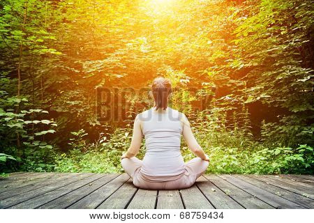 Young woman meditating in a forest sitting on a wooden floor. Zen, meditation, relax, spiritual health, healthy breathing