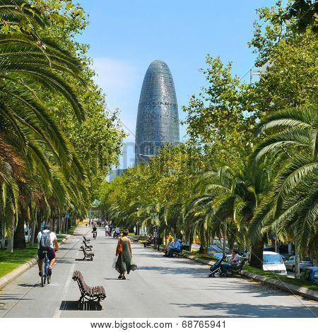 BARCELONA, SPAIN - JULY 14: People walking in Avinguda Diagonal with the Torre Agbar in the background on July 14, 2014 in Barcelona, Spain. This 38-storey tower was designed by famous Jean Nouvel