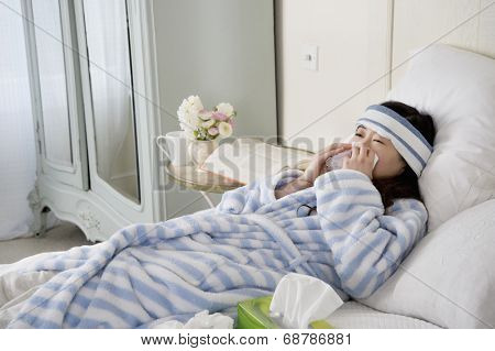 Young woman lying on bed with common cold