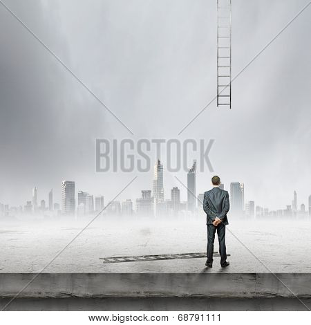 Rear view of businessman looking at broken ladder