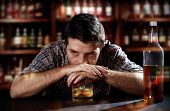 lonely young alcoholic drunk man depressed, wasted thinking about alcohol addiction drinking indoors at bar of an irish pub leaning hands on whiskey glass in alcoholism concept poster