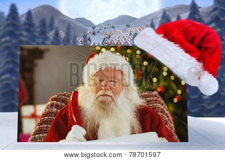 Santa claus writing his list with a quill against cute christmas village under huge full moon