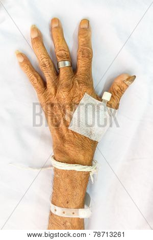 hand of old patient with plug on bed in hospital poster
