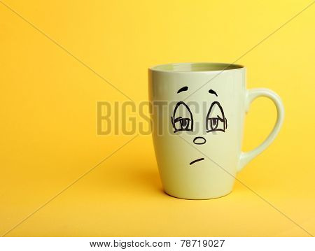 Emotional cup on yellow background