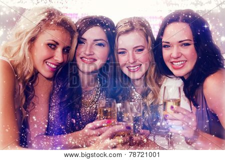 Friends drinking champagne against gold and red lights