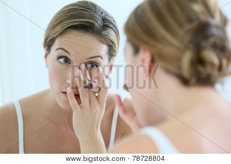 Beautiful blond woman applying concealer around eyes