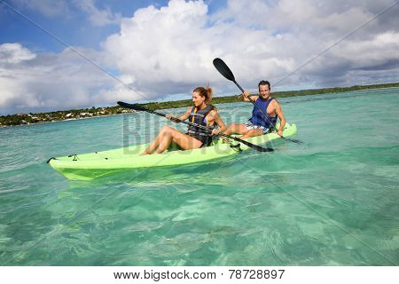 Couple canoeing in lagoon of West French indies