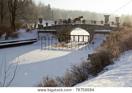 winter sunny landscape with horse-drawn carriage on old bridge