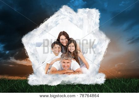 Happy familly looking at the camera against green grass under blue and orange sky