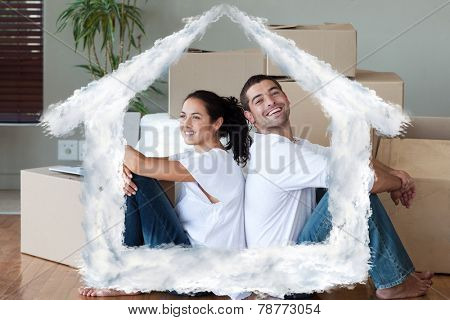 Bright couple with unpacking boxes moving to a new house against house outline in clouds