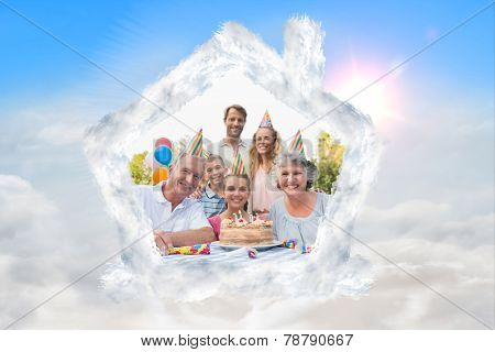 Cheeful family smiling at camera at birthday party against blue sky with white clouds