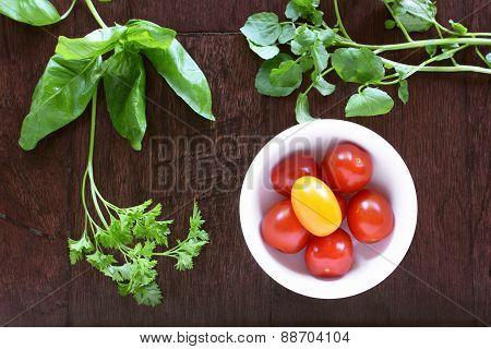 Cherry Tomatoes And Fresh Herbs On Dark Wood