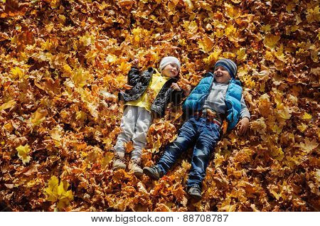 Happy children in autumn park lying on leaves