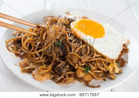 Close-up stir fried char kuey teow with chopstick over wooden background.