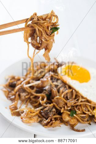 Close-up stir fried char kuey teow on chopstick over wooden background.