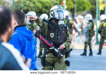 ATHENS, GREECE - APR 16, 2015: Riot police with their shield, take cover during a rally in front of the Athens University, which is under occupation by protesters leftist and anarchist groups.