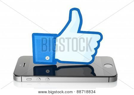 KIEV UKRAINE - MARCH 7 2015: Facebook thumbs up sign printed on paper and placed on iPhone