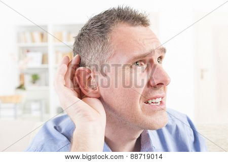 Man wearing deaf aid in ear attempting to hear something poster