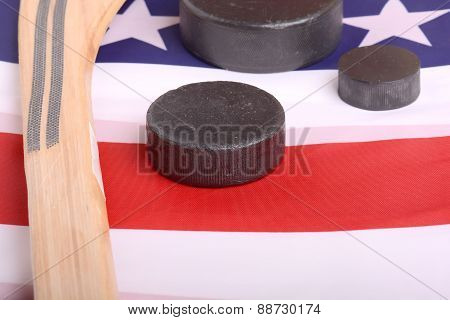 Hockey Equipment Including A Stick And Puck On An American Flag To Infer A Patriotic American Sport.