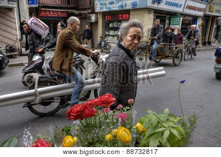 Lively Street Asian City, Townspeople  Ride On Motorcycles And Bicycles.