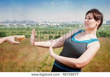 Beautiful plus size woman in sportswear refusing junk food outdoor poster