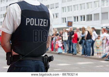 Policeman in front of a crowd