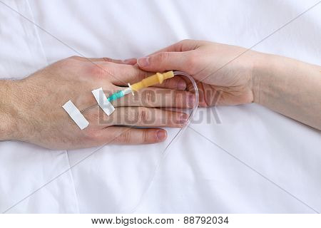 Female hand holding man hand with dropper needle on bed close-up