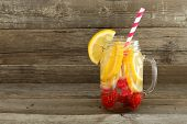 Detox water with lemon and raspberries in a mason jar with straw against a wood background poster