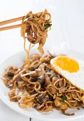 Close-up stir fried char kuey teow on chopstick over wooden background.  poster
